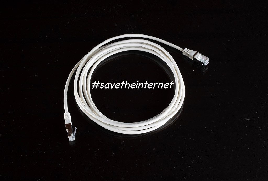 #savetheinternet Text in einem Internetkabel (Lankabel), auf schwarzem Untergrund