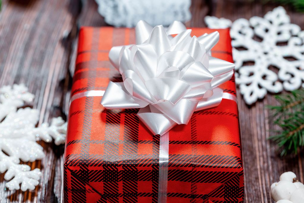 A beautiful gift in red paper with a white bow and branches of a Christmas tree with snowflakes