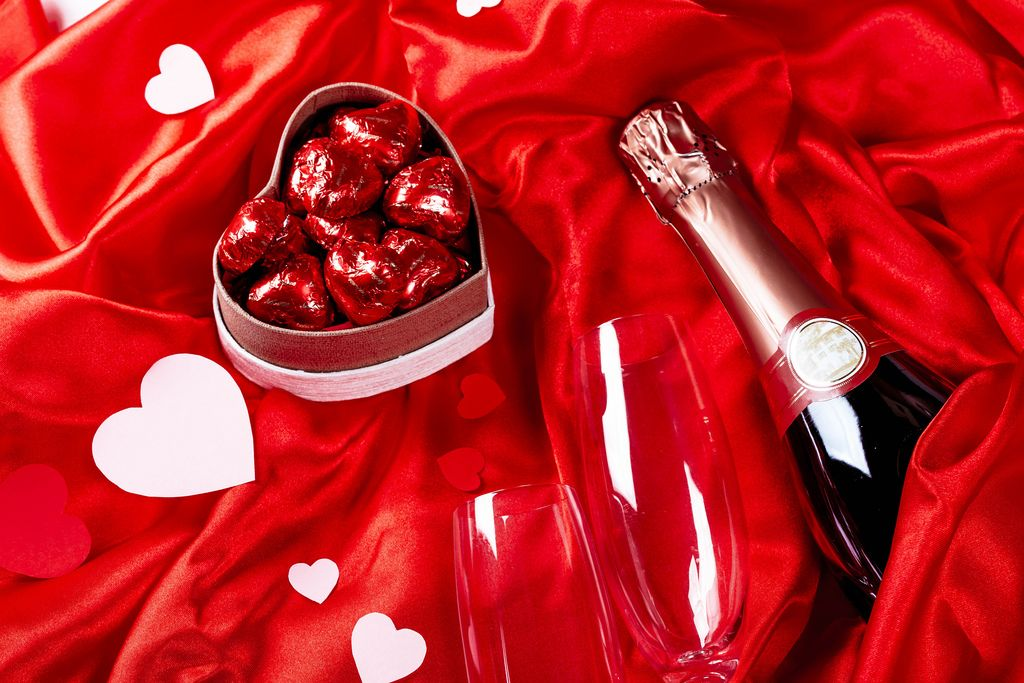 A bottle of champagne with glasses and sweets on a red silk fabric