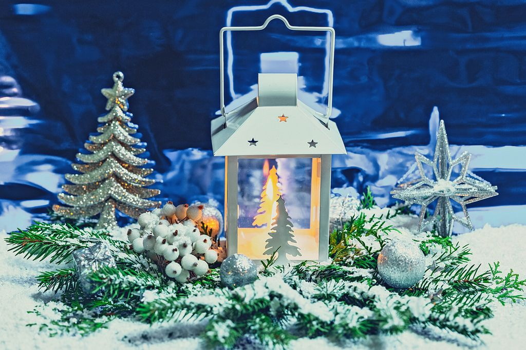 A Christmas lanternis shining on a blue background with branches of a Christmas tree, decor and snow. The concept of magical holidays