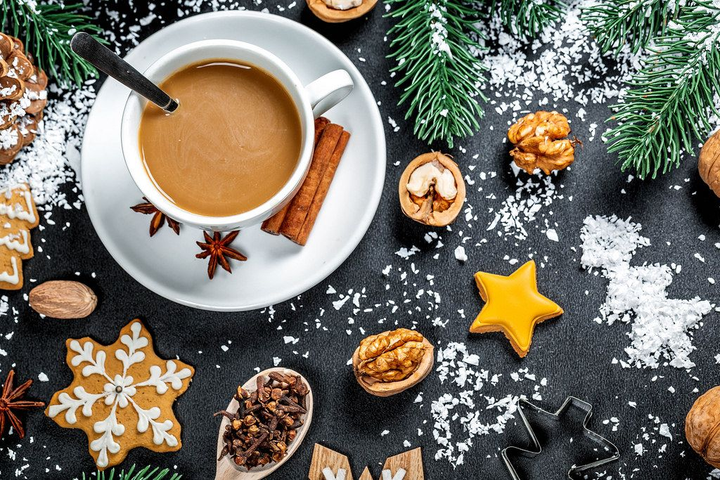 A cup of coffee with gingerbread and winter spices on the background with snow and Christmas tree branches. Winter mood