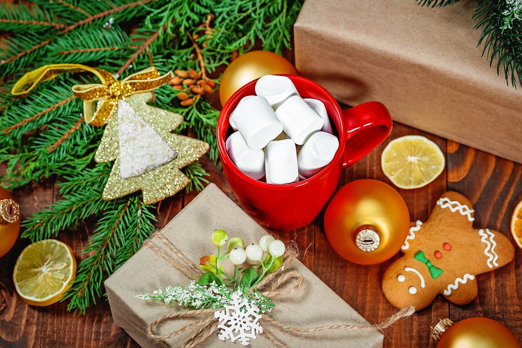 A Cup of coffee with marshmallows, gingerbread man and a gift on a wooden table with Christmas tree branches. Christmas sweets