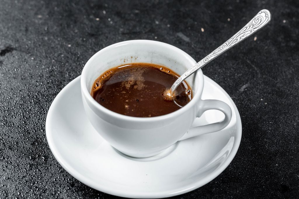A Cup of hot coffee with a coffee spoon on a dark background