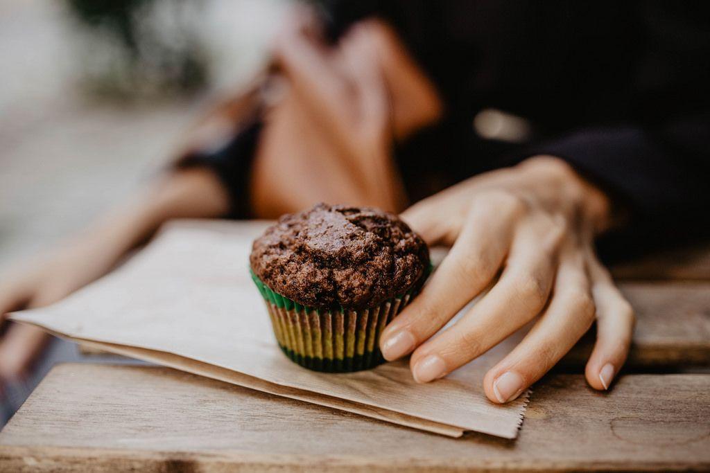 A girl's hand holding a chocolate cupcake.