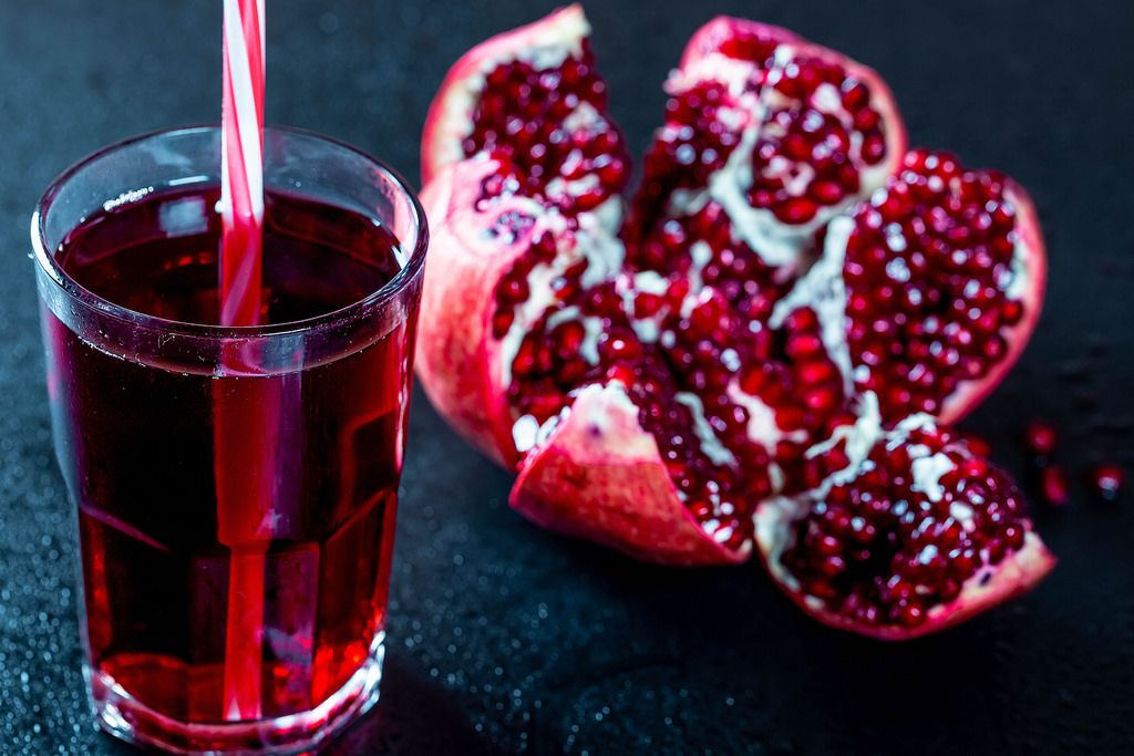 A glass of pomegranate juice with fresh pomegranate on a dark background