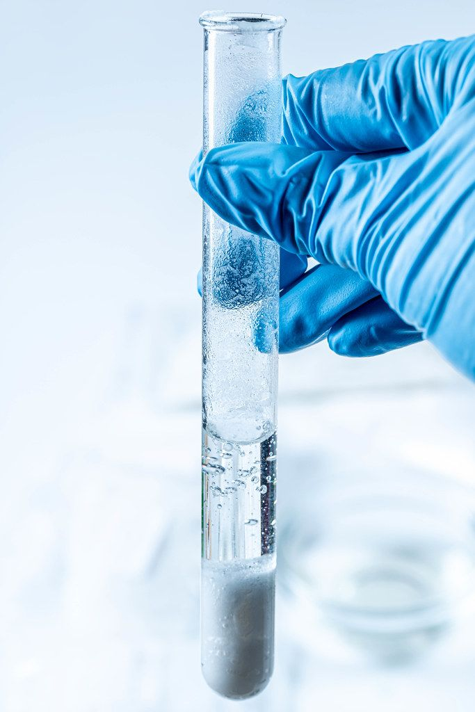 A gloved hand holds a test tube. The concept of observing a chemical reaction (Flip 2020)