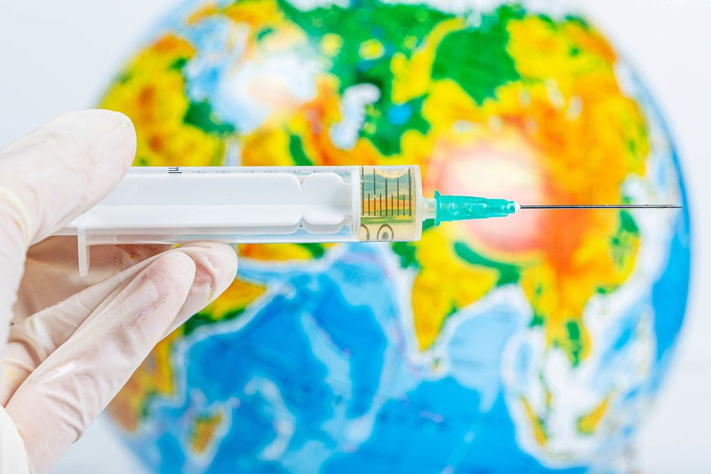 A hand in a glove holds a syringe on a background of the globe. Health protection concept
