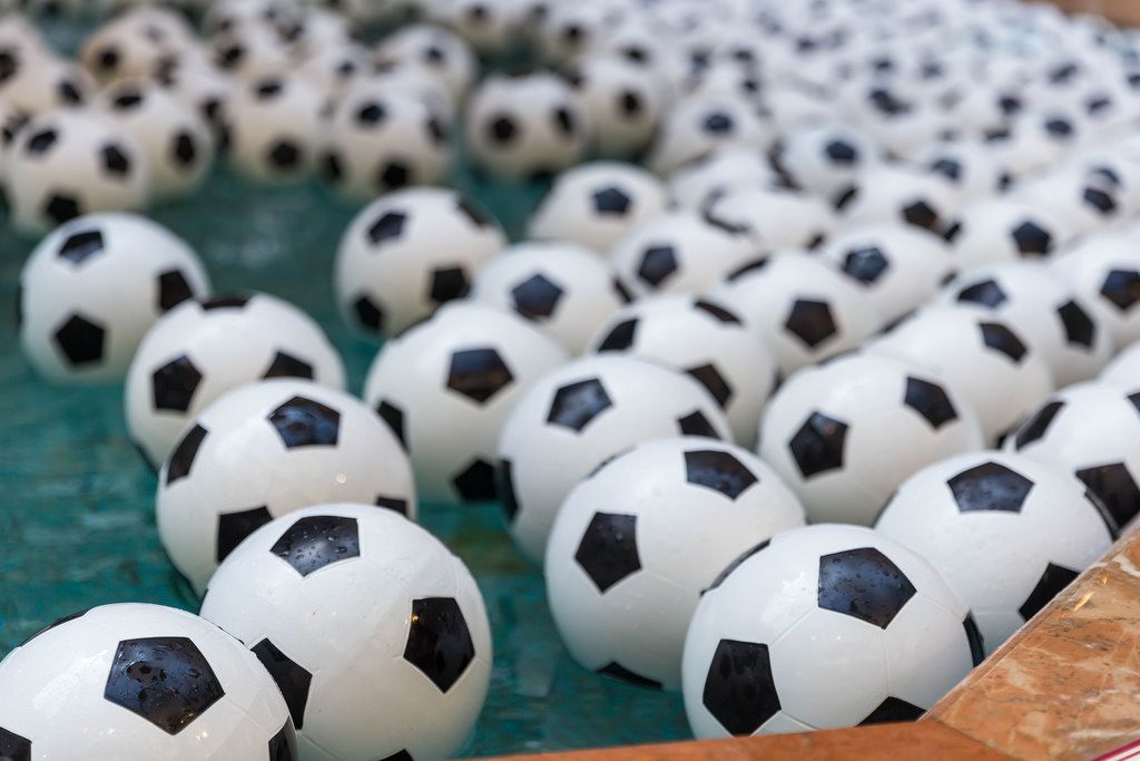 A lot of soccer balls in a fountain