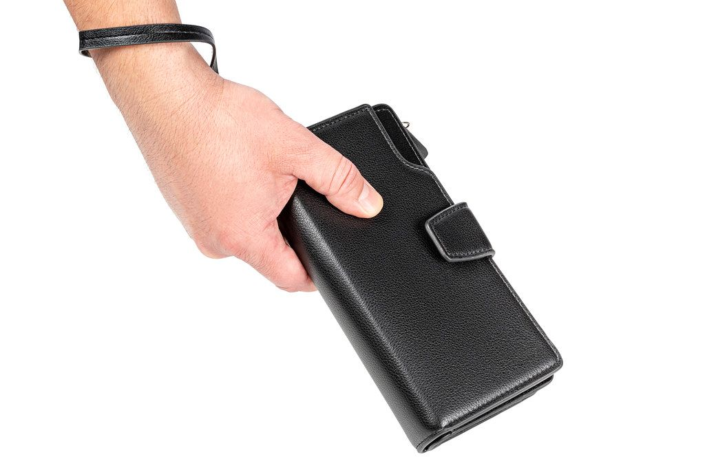 A man holds a black wallet in his hand