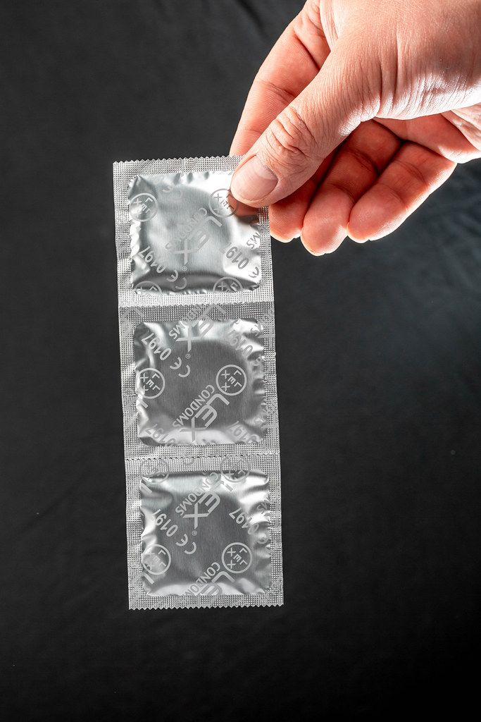 A man holds a pack of condoms on a black background