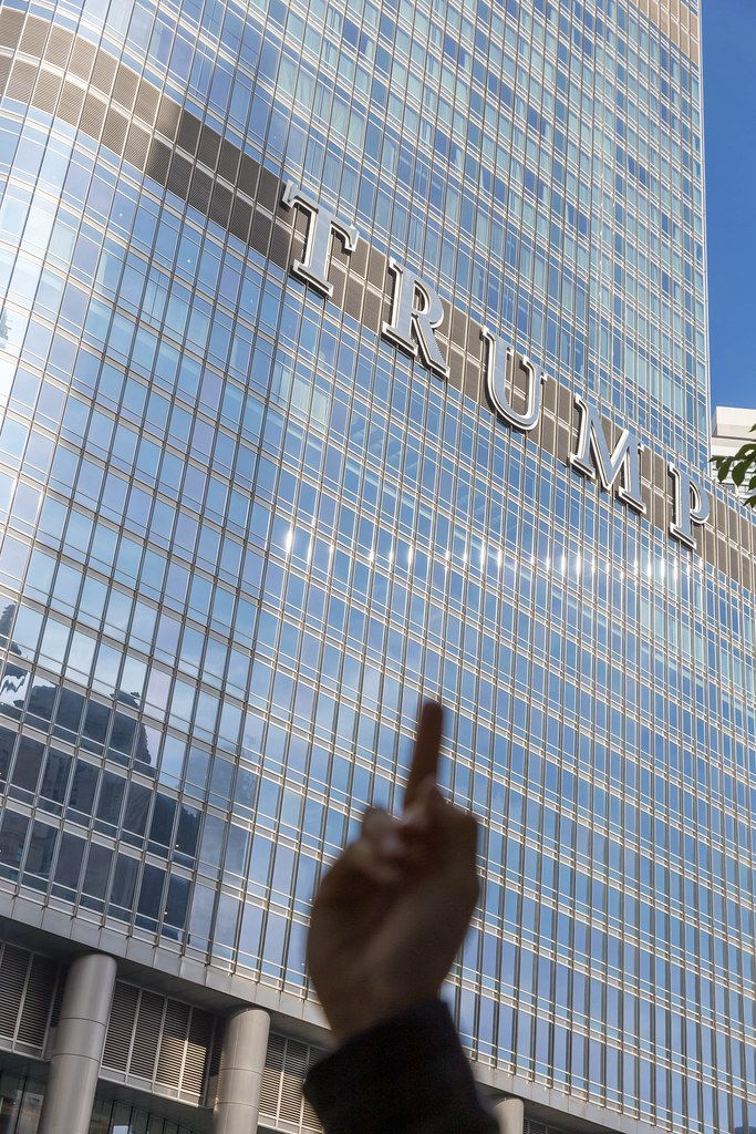 A man shows the middle finger as a political statement against US President Trump in front of the Trump Tower in Chicago