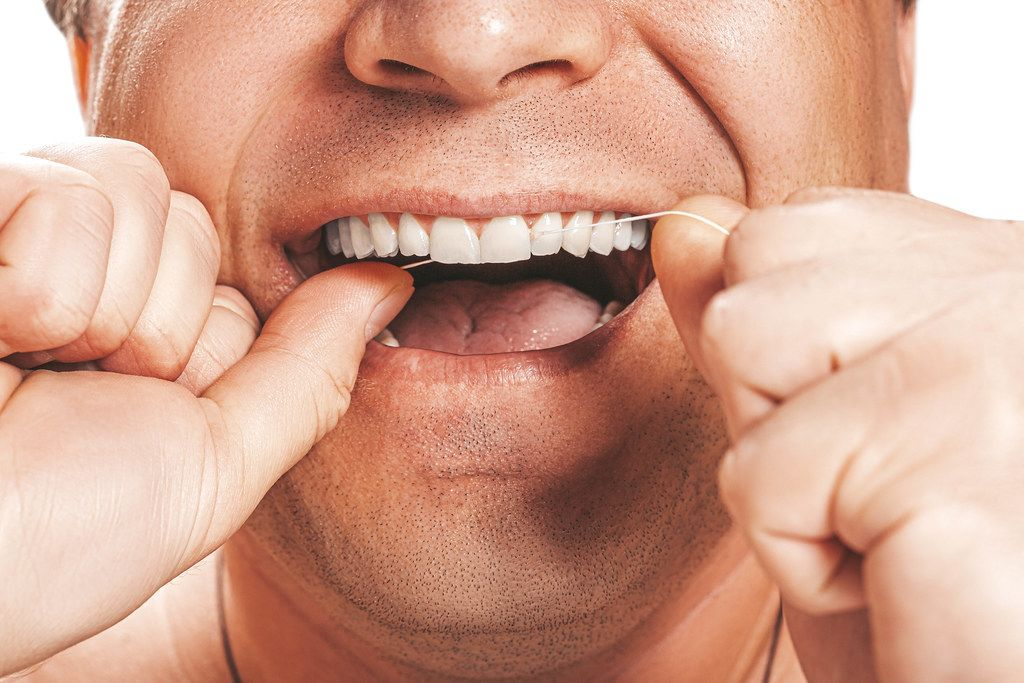 A man uses dental floss to clean his teeth