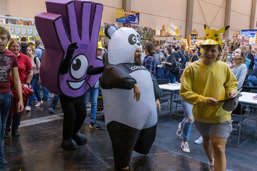 A mascot of the Dobble card game, a man in a panda costume and a girl in a Pokemon mask at the international gaming fair SPIEL 19 in Essen, Germany