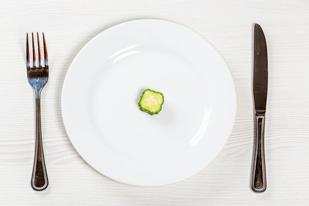 A piece of fresh cucumber on a white plate. The concept of weight loss, diet food