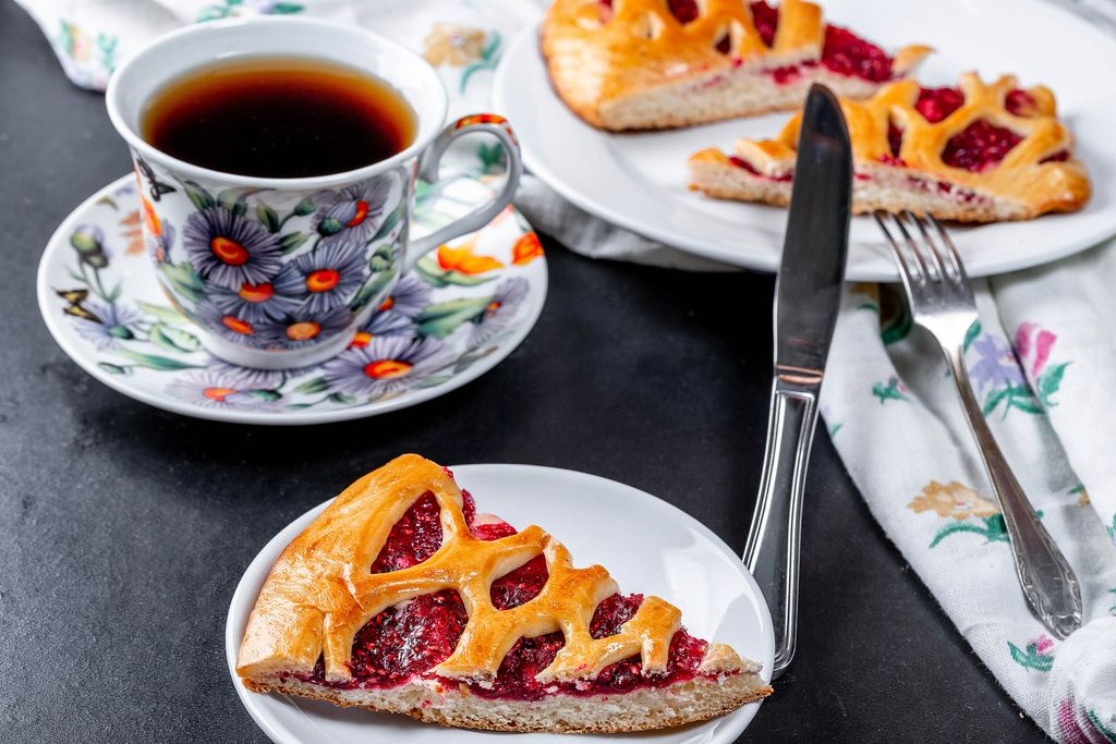 A piece of raspberry pie and a Cup of hot tea