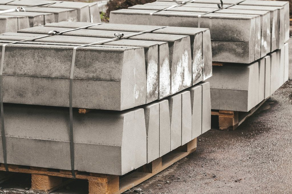 A pile of new road curbs outdoors on wooden pallets. Materials for road construction