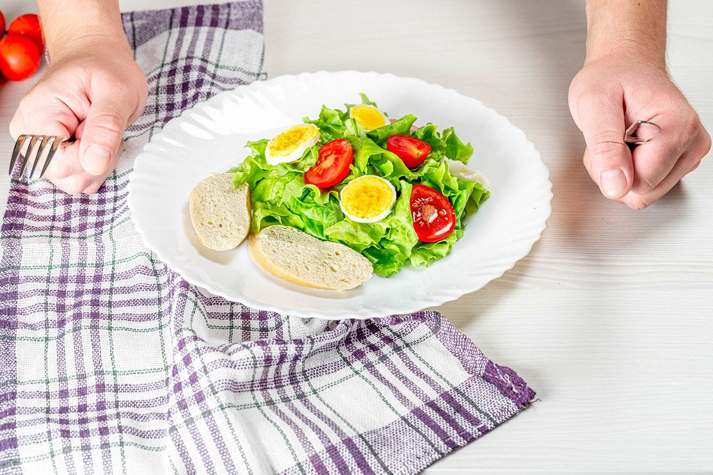 A plate of fresh salad and a man's hands with a knife and fork (Flip 2019)