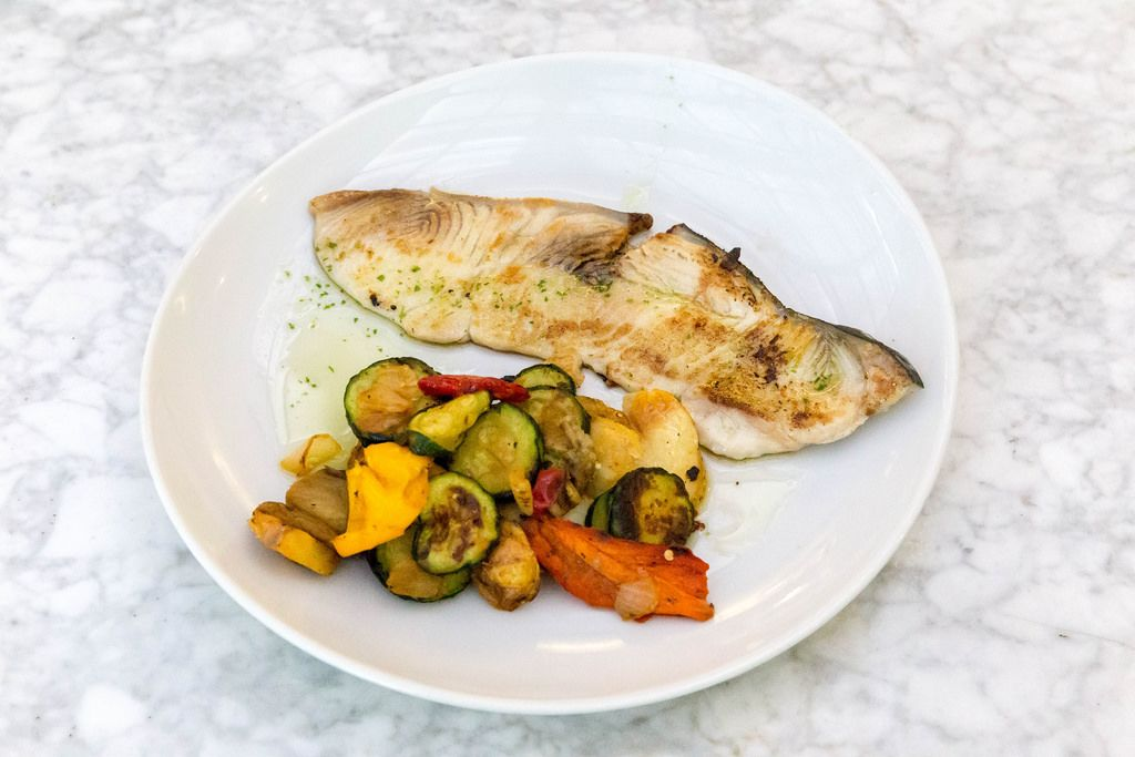 A portion grilled swordfish with vegetables on a white plate