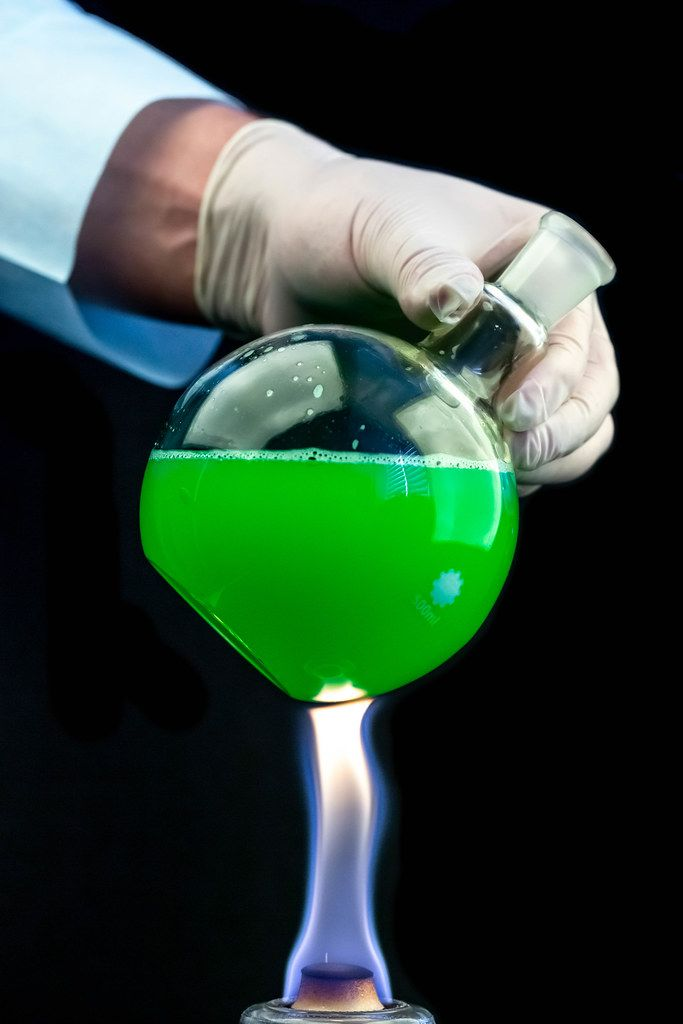 A round flask with a green solution in the hand of a scientist over a fire on a dark background