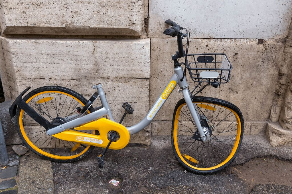 A sharing bike - rental bicycle with a twisted tire