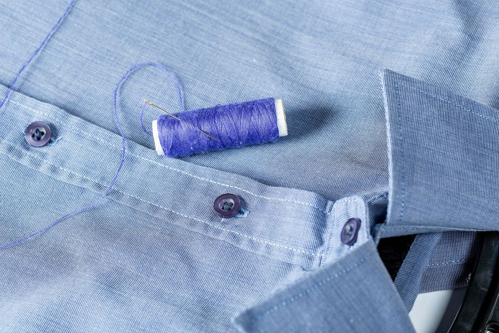 A spool of blue thread and needle on a man's shirt