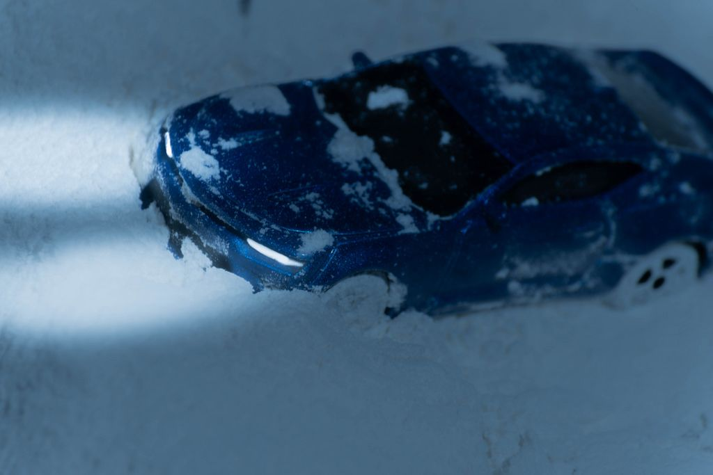A sports car in dangerous driving conditions on a snowy road at dusk