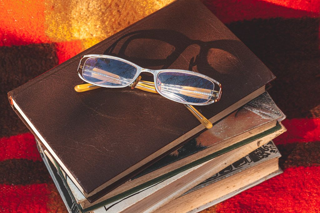 A stack of books and glasses on a blanket. The concept of autumn leisure (Flip 2019)