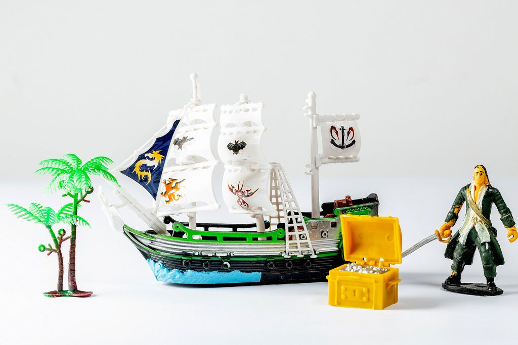 A tiny toy pirate ship with a treasure chest and a statue of a pirate on white background