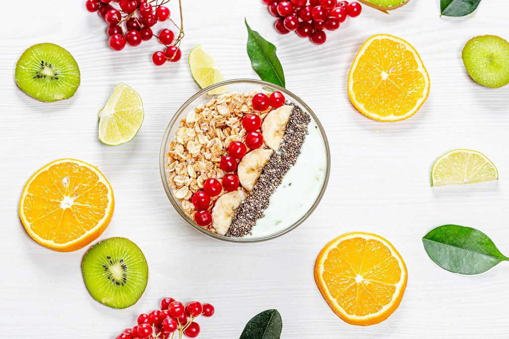 A top view of a bowl of oatmeal on a white wooden background with fresh fruits and berries
