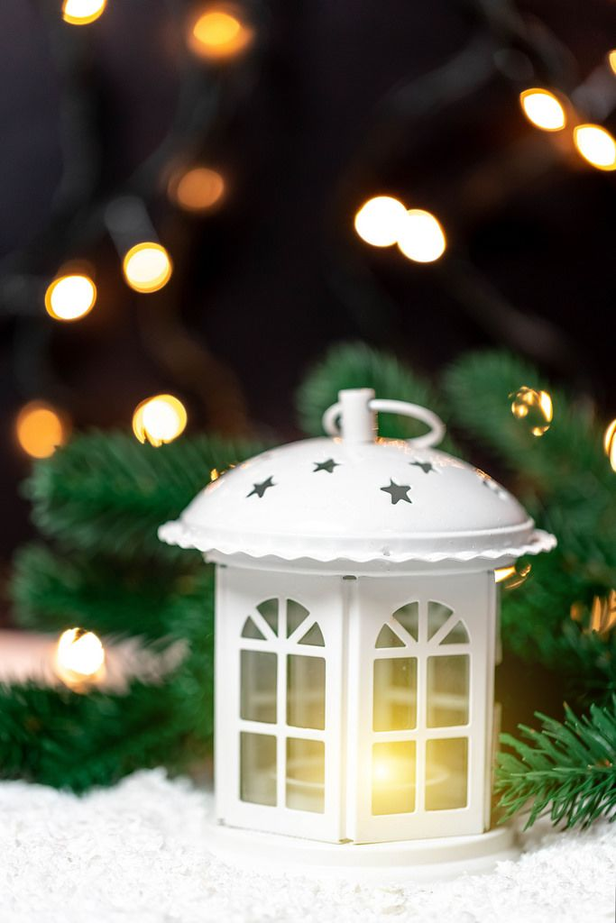 A white christmas lantern with lit candle and tree branches in front of dark background with lights