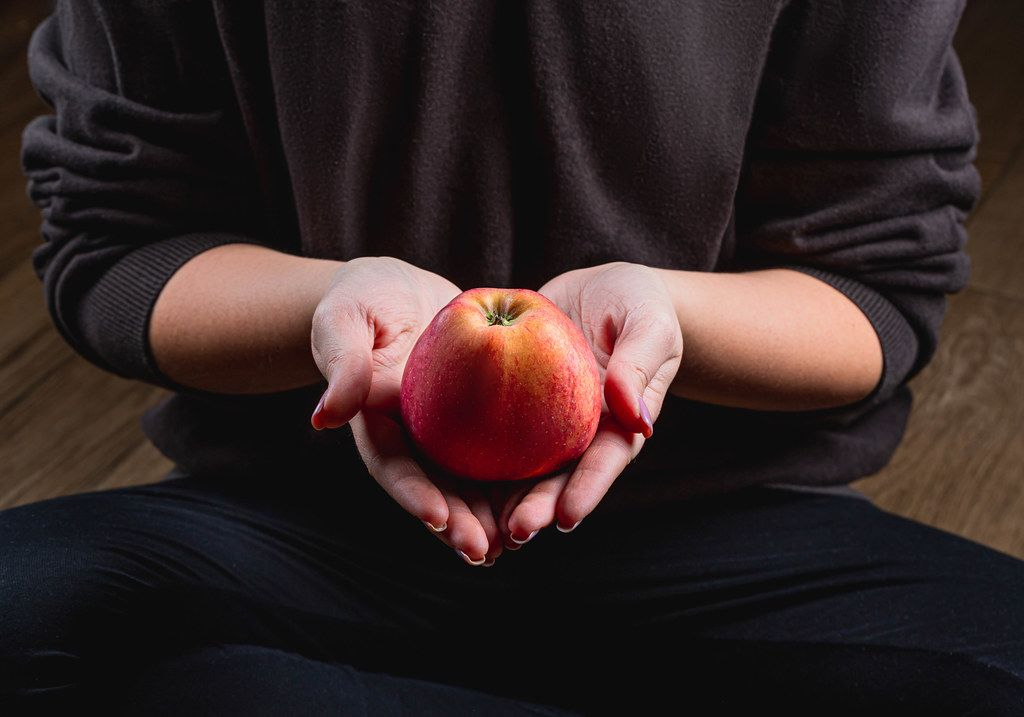 A woman holds a red apple in her hands. Healthy eating concept