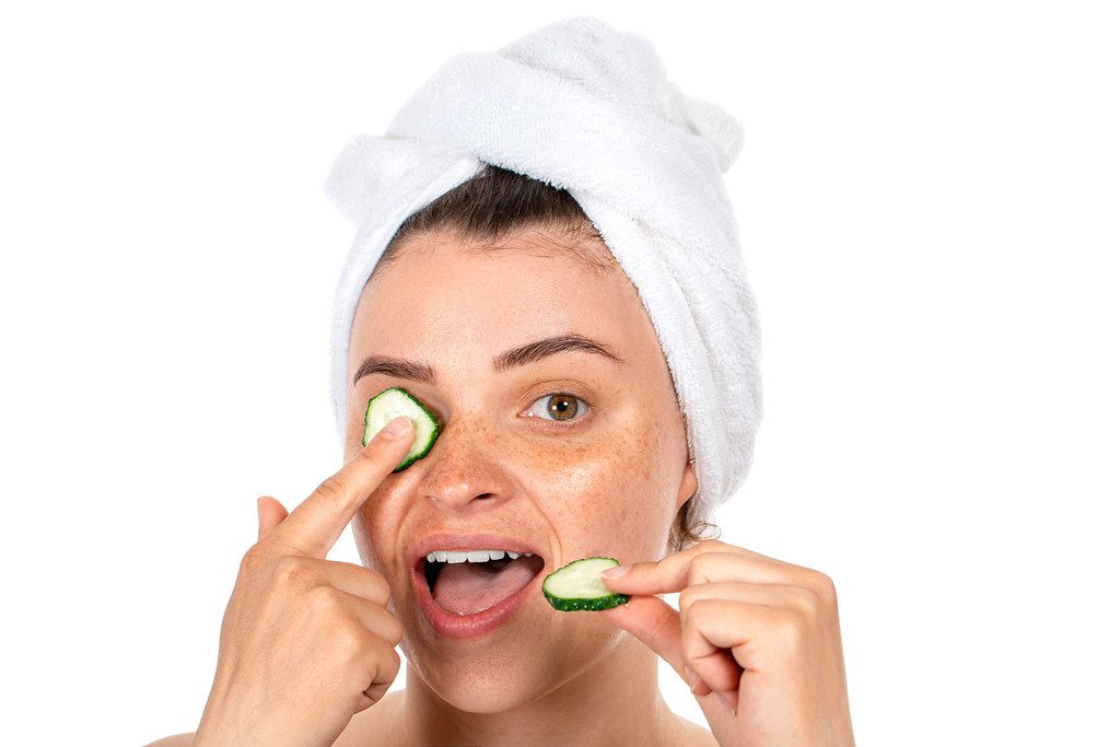 A young woman with a towel on her hair and pieces of fresh cucumbers. The concept of beauty