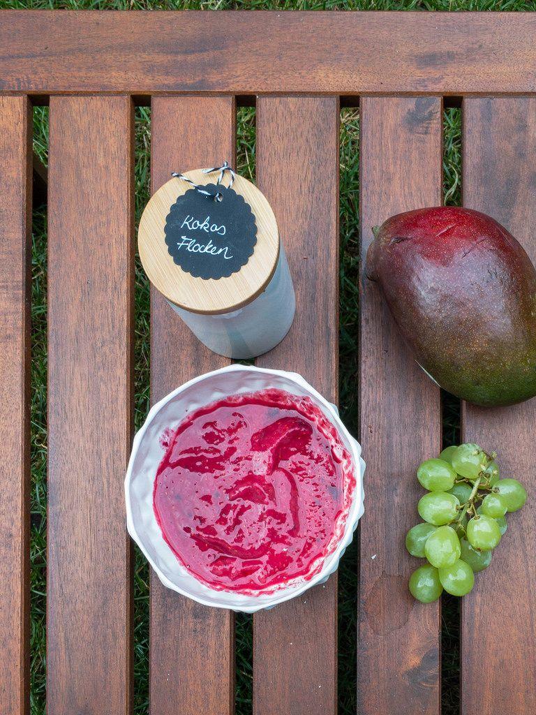 Acai-Grundmasse, Kokosflocken, Weintrauben und eine Mango