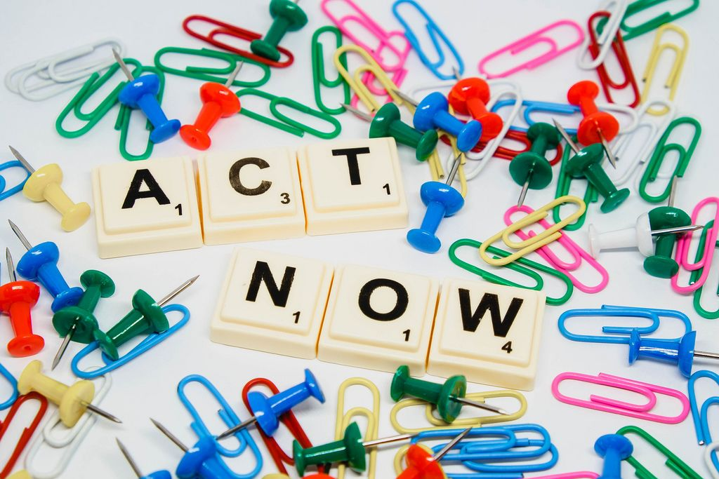 Act Now text surrounded by pins and paperclips