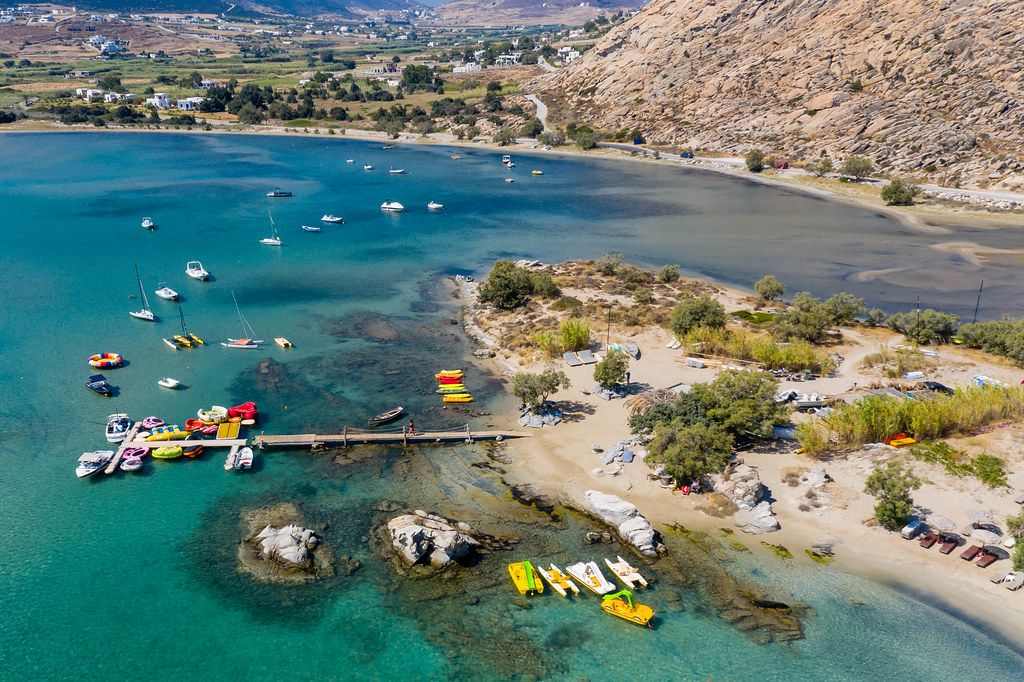 Aerial photo shows the rocky coast of Kolimbithres on Paros, and colorful pedal boats in the Aegean Sea