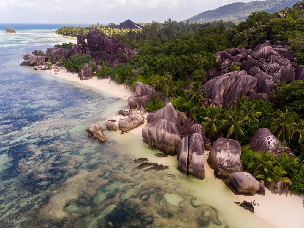 Aerial photography of multicolored granite rocks on Anse Source d'Argent Beach with swimming people in the Indian Ocean, Seychelles