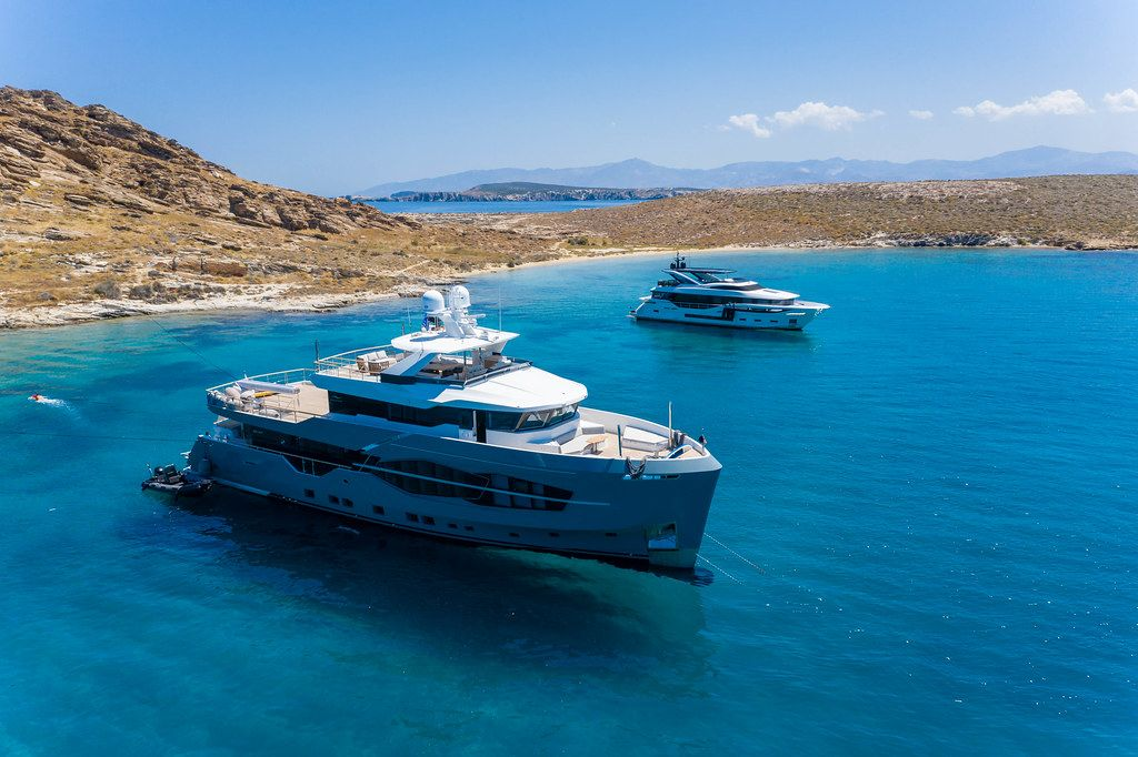 Aerial shot of luxurious yachts and 32 meters Numarine yacht Q.M. on the blue sea in the Aegean Sea, at Cape Korakas on Paros, Greece