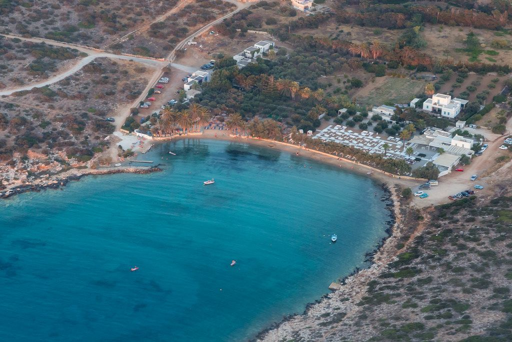 Aerial view of a bay with beach section and blue sea, in front of the Greek island Paros