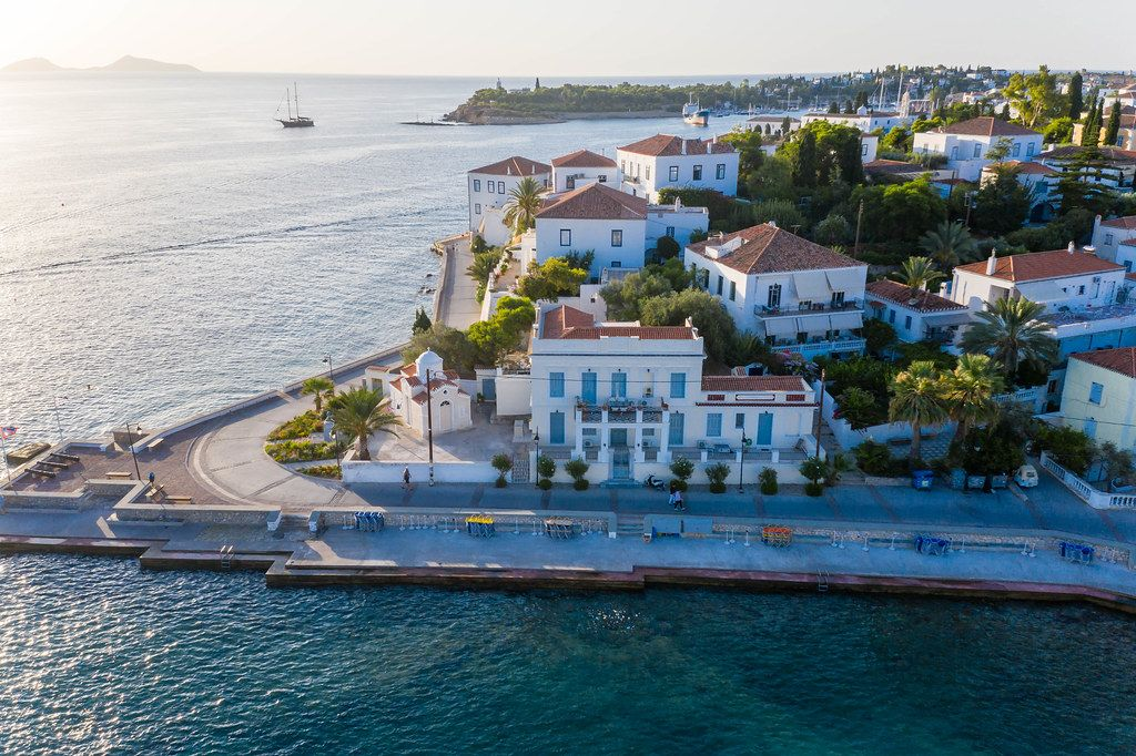 Aerial view of a coastal path & Church at Agios Mamas Beach, next to aristocratic villas on the Mediterranean island Spetses, Greece, in the Saronic Gulf