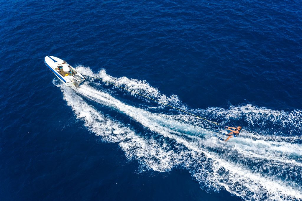 Aerial view of a standing water skier behind a sports boat on the Agogic Gulf