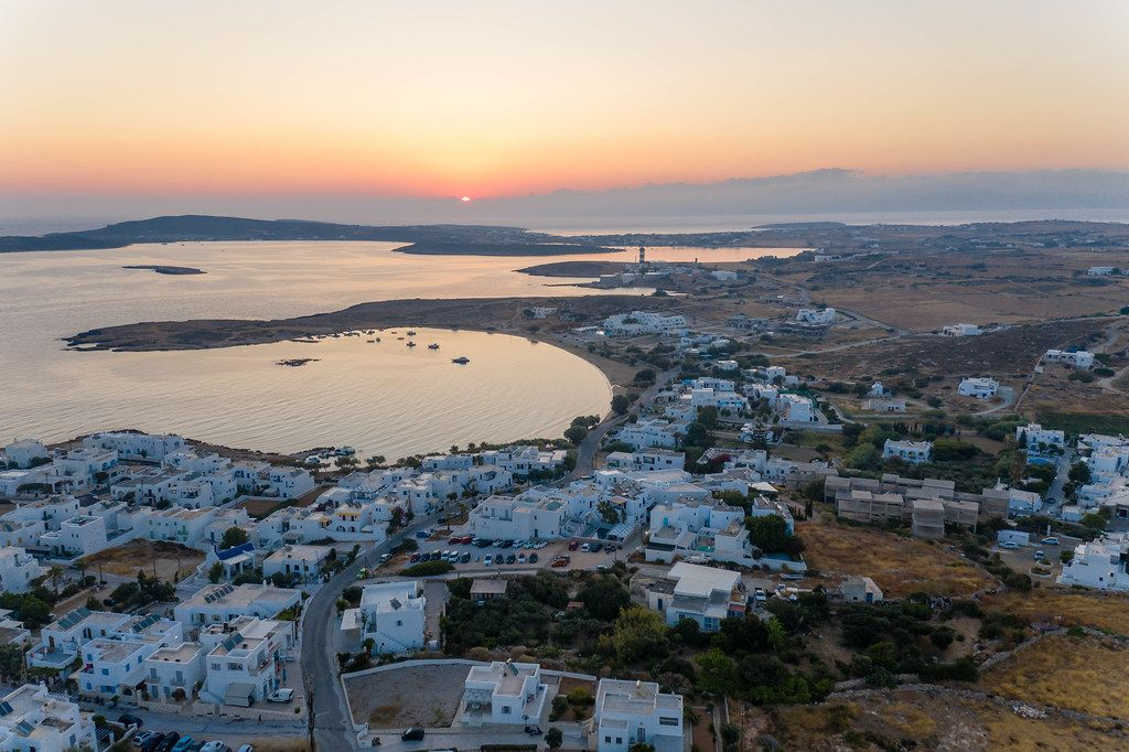 Aerial view of a sunset at the horizon of Aegean Sea and small island town Naoussa on Paros, Greece