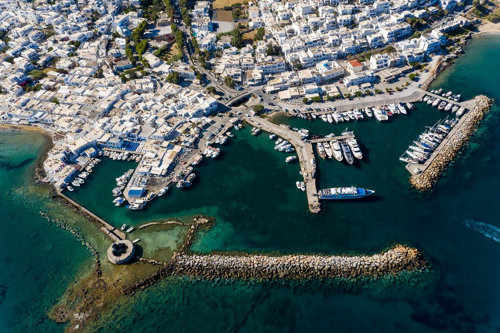 Aerial view of a Venetian castle ruin in the deep blue Mediterranean Sea, in front of the sea port Naoussa on the Greek island Paros