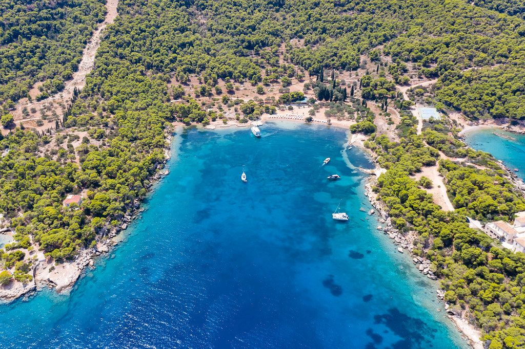 Aerial view of luxury yachts in the blue sea at Ekklisia Analipsi beach at Spetses, Greece