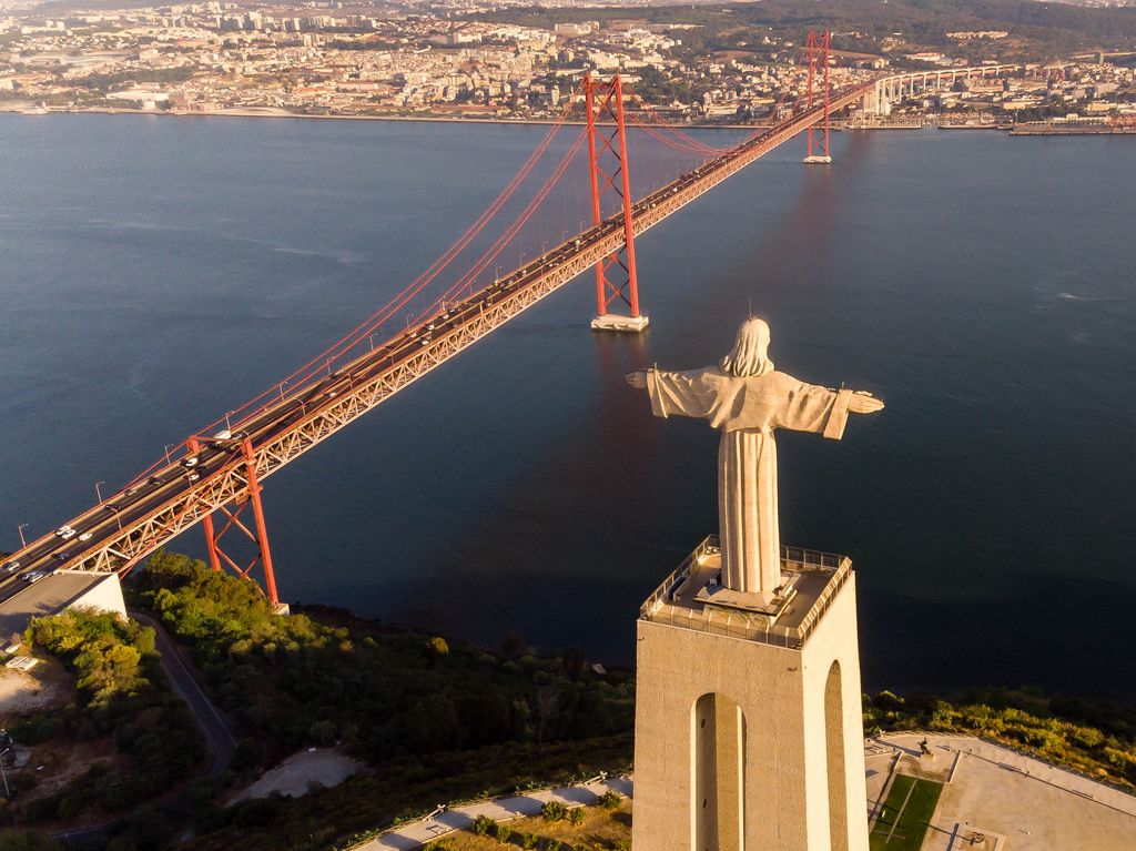 Aerial view of the Cristo Rei statue looking over the Tajo river onto Lissabon with Ponte 25 de Abril bridge