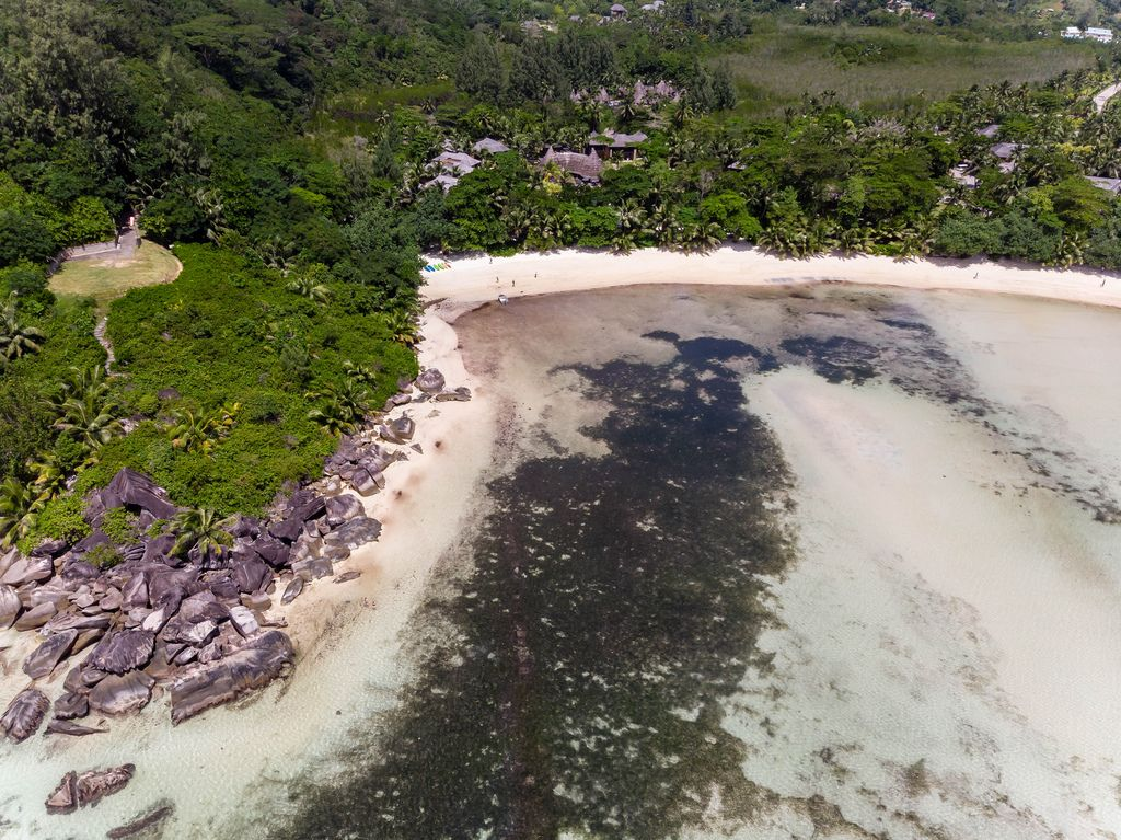 Aerial view of the granite stones and helipad at the coast of Port Glaud in Mahé in the Indian Ocean, Seychelles
