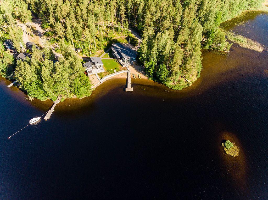 Aerial view shows luxury holiday houses Kiuasniemi Villas, Villa Paapuuri & Villa Jolla with privat wooden jetties at lake Päijänne, vis-à-vis Kalainsaari island