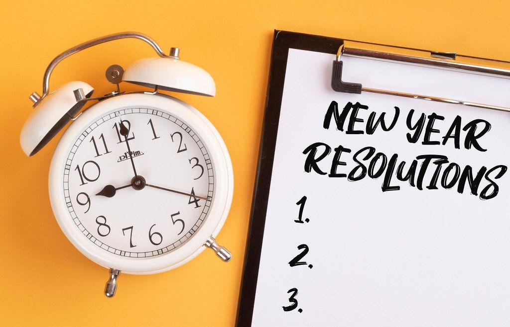 Alarm clock with handwritten New Year Resolutions List on clipboard
