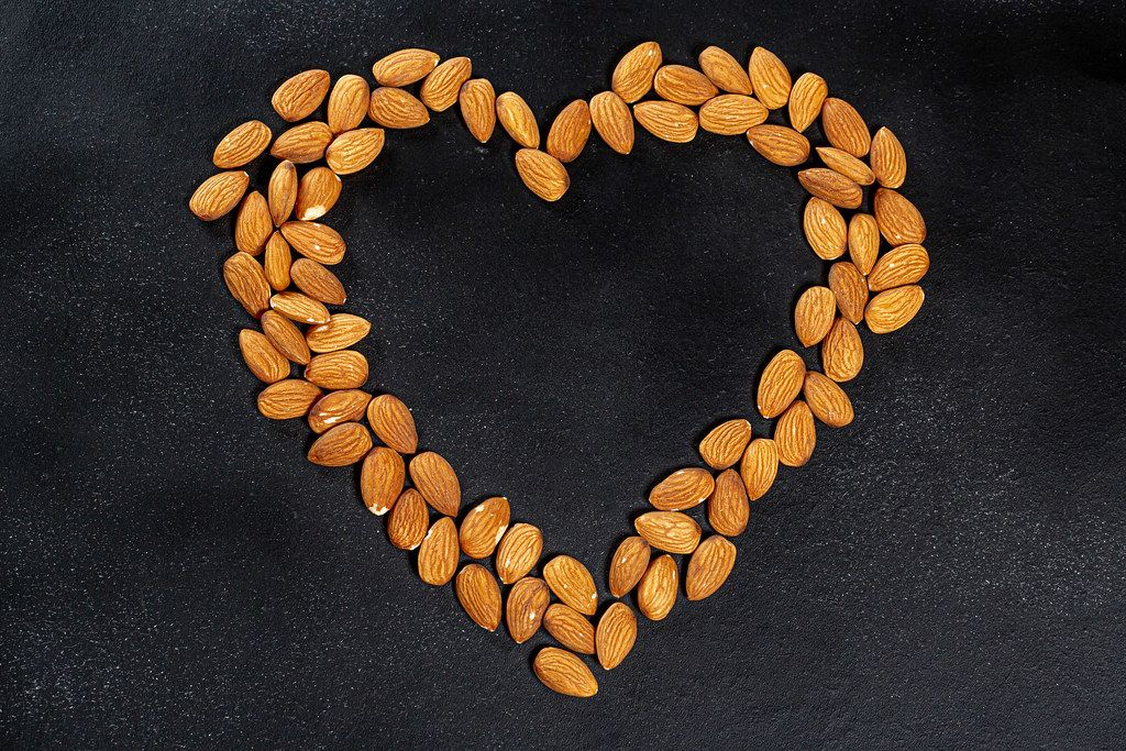 Almond nuts on a black background lined in the shape of a heart. Top view