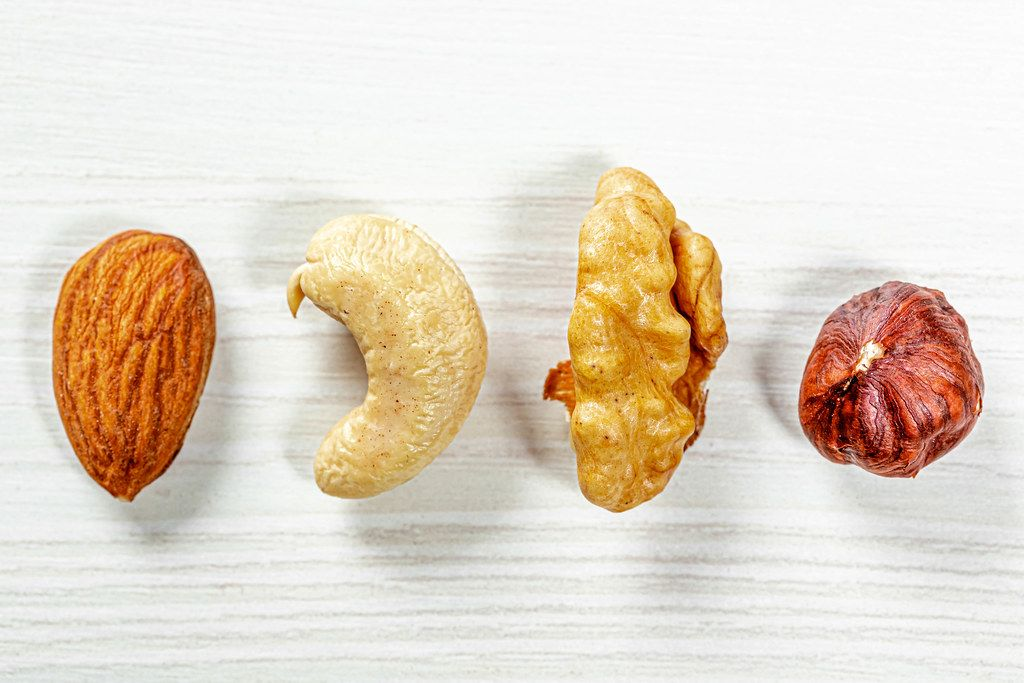 Almonds, cashews, hazelnuts, walnuts on white wooden background. Top view