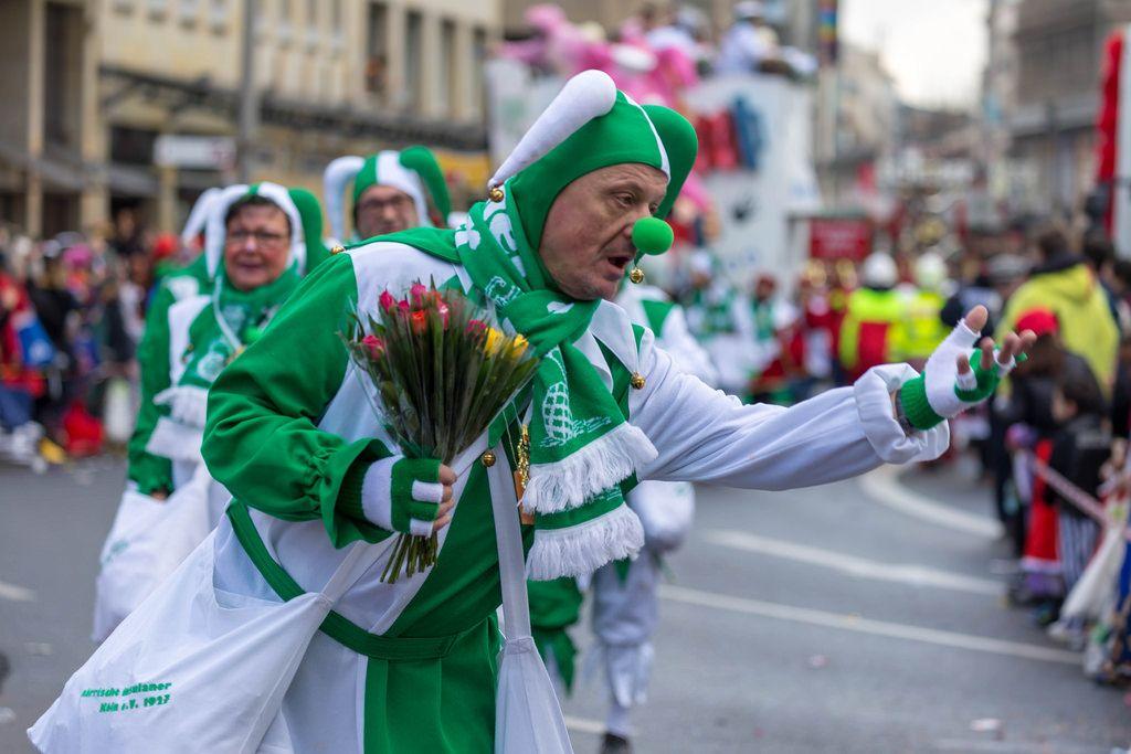 Als Narr verkleideter Mann in grün-weiß mit Blumen - Kölner Karneval 2018